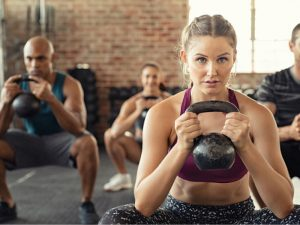 A gym instructor holding a kettle bell with her clients