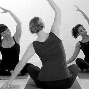 A female gym instructor talking her client yoga exercise